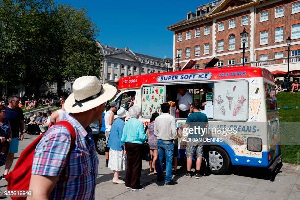 People queue at an ice cream van as they soak up the sun in Richmond south west London on May 7 2018 Temperatures on Monday were predicted to reach...