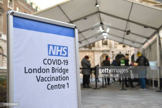 People queue at an NHS Covid-19 vaccination centre for the Pfizer-BioNTech Covid-19 vaccine in London on December 30, 2020 as cases of the virus...