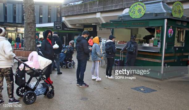 People queue at an outdoor noodle bar at the city centre. On the first weekend of new coronavirus restrictions, the City of Coventry is in the Tier 3...