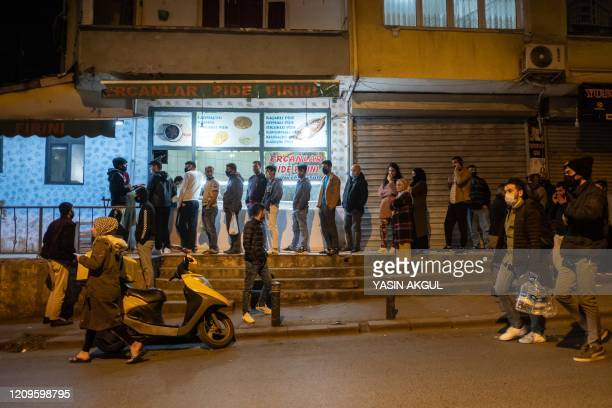 People queue at shops for food and supplies shortly before the curfew in Istanbul on April 10 as Turkey ordered citizens to stay at home for 48 hours...
