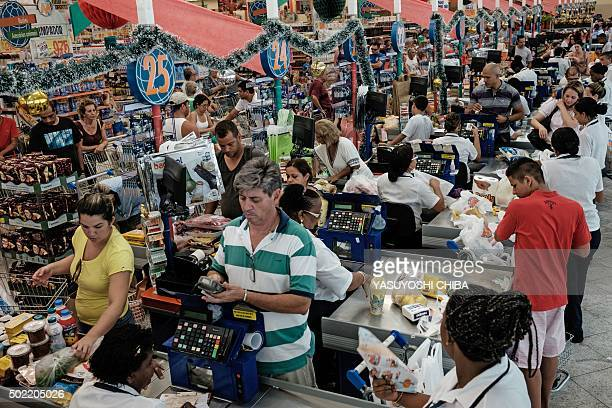 People queue at the checkouts of a supermarket in Rio de Janeiro Brazil on December 21 as they buy groceries for Christmas AFP PHOTO / YASUYOSHI...