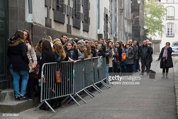 People queue at the entrance of Riom courthouse near ClermontFerrand central France on November 16 to attend a hearing of the trial of Cecile...