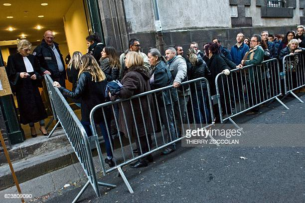 People queue at the entrance of the Riom courthouse near ClermontFerrand central France on November 17 to attend a hearing of the trial of Cecile...
