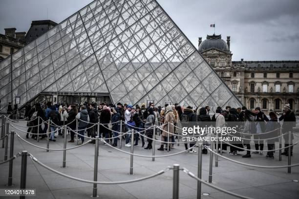 People queue at the Pyramide du louvre entrance on February 28, 2020 in Paris.