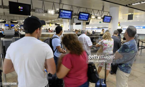 People queue at the Ryanair checkin desk at Brussels Airport in Zaventem on July 25 during a strike of cabin personnel of Irish lowcost airline...