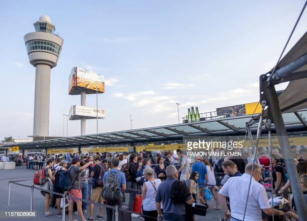 People queue at the taxi rank at AmsterdamSchiphol airport southwest of Amsterdam as a problem with refuelling grounded several dozen planes and...