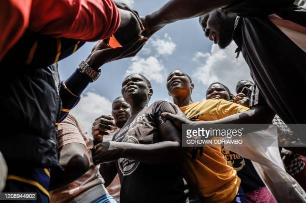 People queue during a food distribution by Team Pangaj a Kenyan voluntary group delivering flour beans milk and juice for about 900 people at the...