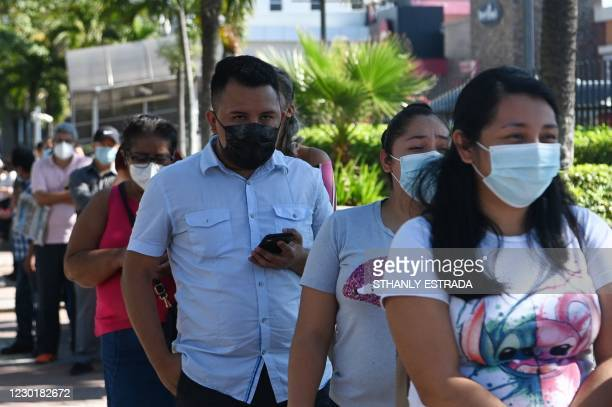 People queue for a free COVID-19 test at a diagnostic booth in San Salvador on December 17, 2020. - The Salvadoran government announced a massive...