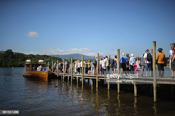 People queue for a pleasure boat ride on Derwent Water on August 17 2016 in Keswick England The Lake District continues to recover after the...