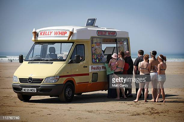 People queue for an icecream van as they enjoy the fine weather in Polzeath near Padstow on April 21 2011 in Cornwall England The UK is currently...