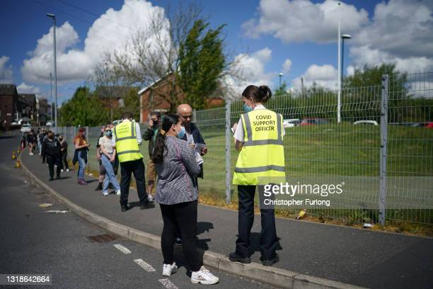 People queue for Covid-19 vaccinations at the ESSA academy in Bolton where mass vaccinations are taking place to try and combat rising levels of the...