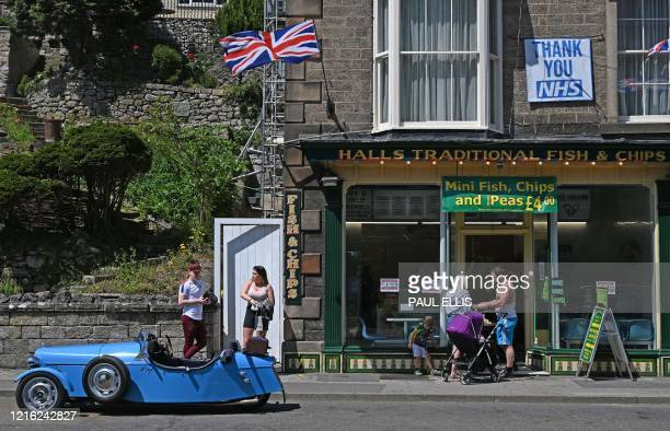 People queue for fish and chips in Matlock Bath in the Peak District in northern England on May 30, 2020 after the announcement of Britain's first...