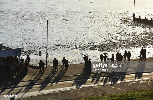 People queue for food and drink at a take away food kiosk on the seafront on January 09, 2021 in Southend, England. With a surge of covid-19 cases...