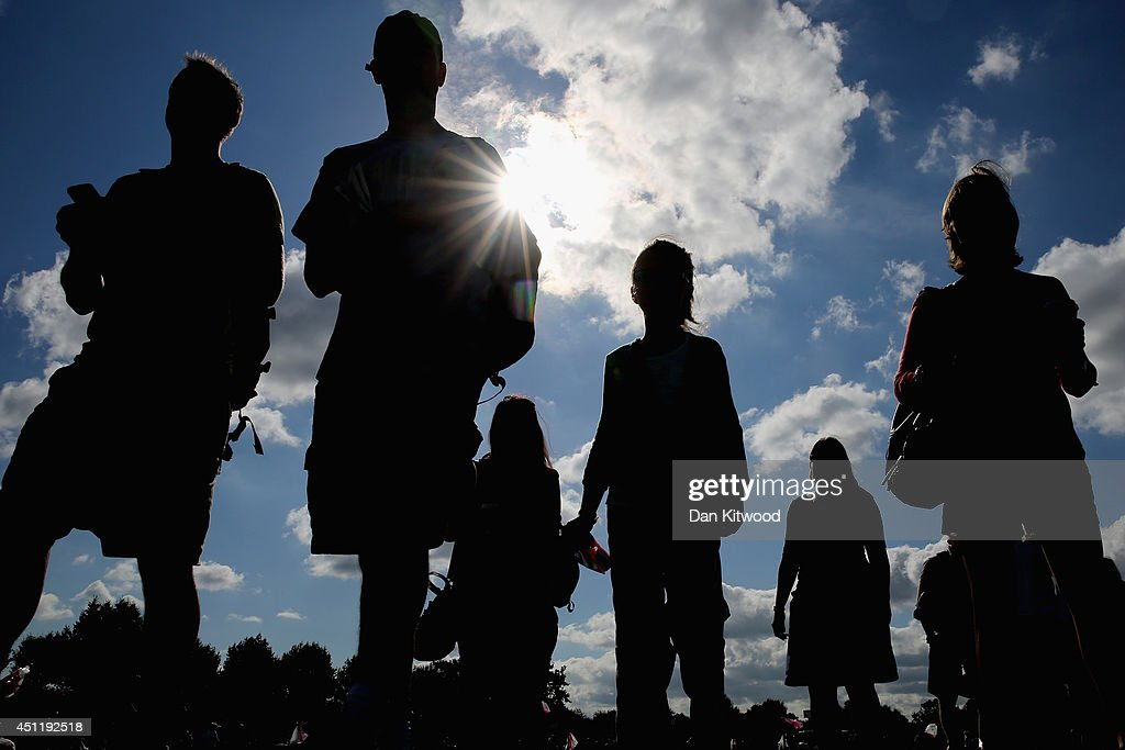 People queue for ground passes in a field adjacent to the 'All England Lawn Tennis and Croquet Club' ahead of the start of day three of the Wimbledon Lawn Tennis Championships, on June 23, 2014 in London, England.
