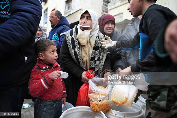 People queue for meals on January 9 2017 in Aleppo Syria Bashar alAssad administration backed by Russia recaptured the area in eastern Aleppo where...
