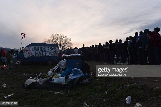 People queue for soups distributed by 'No borders' activists at the makeshift camp at the GreekMacedonian borders near the village of Idomeni where...