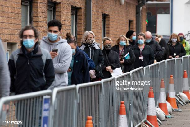 People queue for the Pfizer-BioNTech Covid-19 vaccine at Cardiff and Vale Therapy centre on Splott Road on January 19, 2021 in Cardiff, Wales. Public...