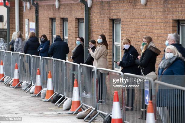 People queue for the Pfizer-BioNTech Covid-19 vaccine at Cardiff and Vale Therapy centre on Splott Road on January 21, 2021 in Cardiff, Wales. Wales...