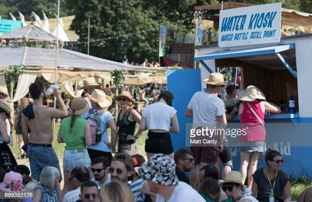 People queue for water as temperatures reach record levels at the Glastonbury Festival at Worthy Farm in Pilton on June 21 2017 near Glastonbury...