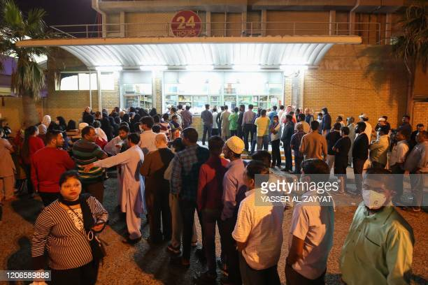 People queue in front of a bakery in Kuwait City on March 11, 2020. - Kuwait will suspend all commercial flights leaving from and arriving at Kuwait...