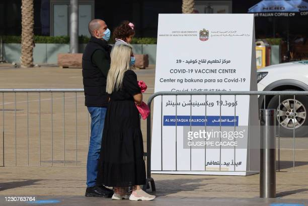 People queue in front of a designated COVID-19 vaccination center at Dubai's financial center district, in the United Arab Emirates, on January 24,...