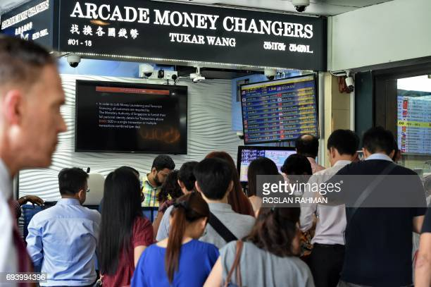 People queue in front of the money changer at the financial district in Singapore on June 9 2017 The pound plunged almost two percent on June 9 as...