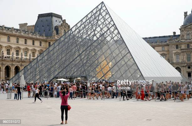 People queue in front of the Pyramid of the Louvre on July 05 2018 in Paris France After two dark years following the terrorist attacks of 2015 the...