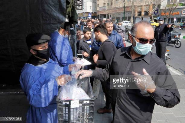 People queue in line to receive packages for precautions against COVID-19 coronavirus disease provided by the Basij, a militia loyal to Iran's...