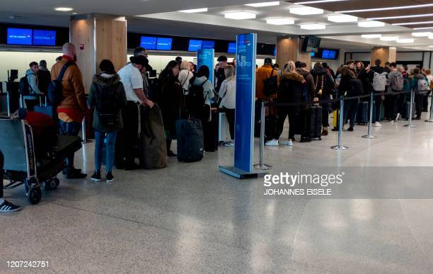 People queue in the departure hall of Terminal 7 at JFK airport on March 15, 2020 in New York City. - Chaos gripped major US airports Sunday as...