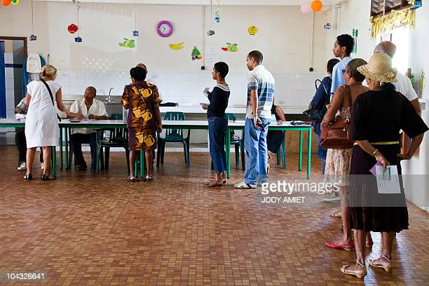 People queue in the polling station of Cayenne on the French South American territory of Guiana on January 10 for the referendum on the status and...