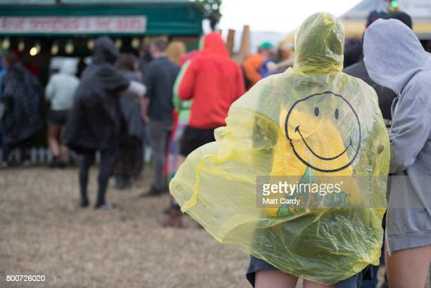 People queue in the rain at the Glastonbury Festival site at Worthy Farm in Pilton on June 25 2017 near Glastonbury England Glastonbury Festival of...