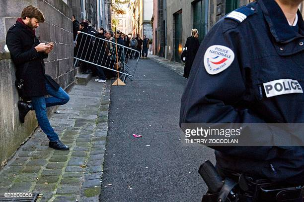 People queue next to a policeman at the entrance of the Riom courthouse near ClermontFerrand central France on November 17 to attend a hearing of the...