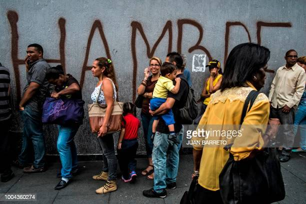 People queue next to a wall with a graffiti reading Hunger in Caracas on July 23 2018 Amid the financial and humanitarian crisis in Venezuela the...