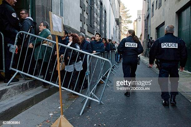 People queue next to policemen at the entrance of the Riom courthouse near ClermontFerrand central France on November 17 to attend a hearing of the...