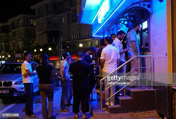 People queue on a banks ATM in July 16 2016 in Istanbul Turkey Istanbul's bridges across the Bosphorus the strait separating the European and Asian...