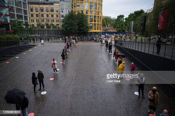People queue on socially distanced marker points as they wait for the doors of the Tate Modern gallery to open, on July 27, 2020 in London, England....