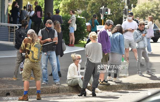 People queue outside a benefits payment centre in Sydney on March 23, 2020. - With the imminent closure of pubs, restaurants, cafes and entertainment...