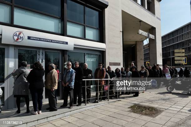 People queue outside a branch of Greeces Public Power Corporation to pay their bills in Thessaloniki on March 5 2019 Greece is setting the stage for...