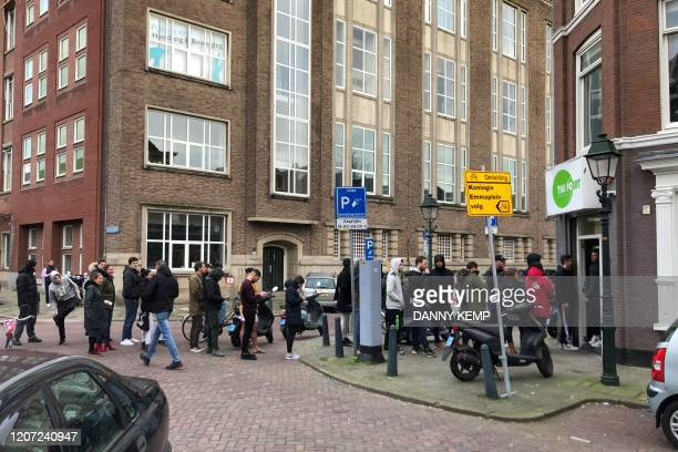 People queue outside a cannabis coffee shop on March 15 in The Hague, after the Dutch government ordered the closing of all schools, bars,...