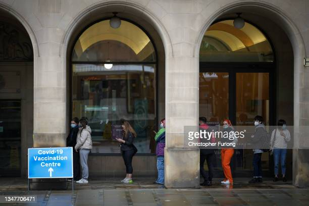 People queue outside a Covid-19 vaccination hub in Manchester city centre on October 20, 2021 in Manchester, United Kingdom. The head of the NHS...