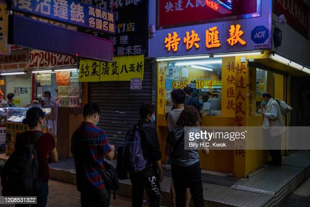 People queue outside a Currency exchange store during a coronavirus on March 28 2020 in Hong Kong China Latest statistics showed Hong Kong tourist...