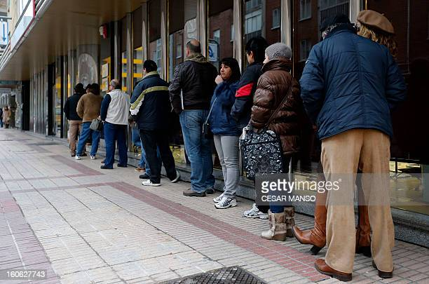 People queue outside a government employment office in Burgos on February 4 2013The number of Spaniards officially registered as unemployed rose to...
