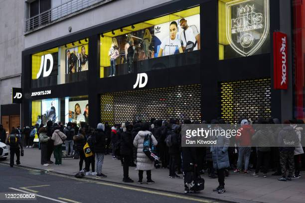 People queue outside a JD Sports shop on Oxford Street as retail reopens after coronavirus restrictions ease on April 12, 2021 in London, United...