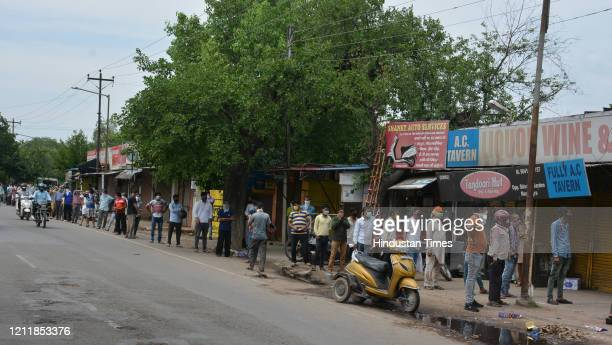 People queue outside a liquor shop during nationwide lockdown at Manimajra on May 4 2020 in Chandigarh India