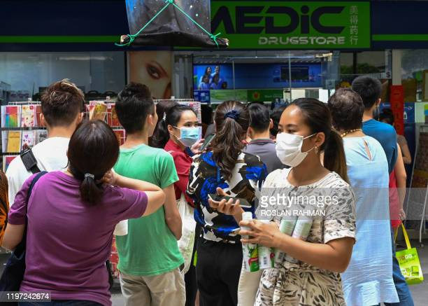 People queue outside a pharmacy to purchase protective face mask, thermometer and hand sanitizer in Singapore on January 29, 2020. - Singapore has so...