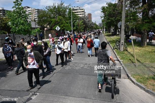 People queue outside a polling station during a constitutional referendum voting in Santiago, on October 25, 2020. - A year to the day after more...