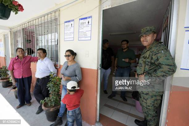 People queue outside a polling station in the Quito neighborhood of Zambiza to cast their votes in a referendum called by President Lenin Moreno on...