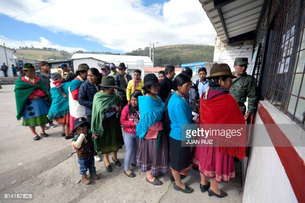 People queue outside a polling station set up at a school in the Ecuadorean town of Cangahua northeast of Quito to cast their votes during a...