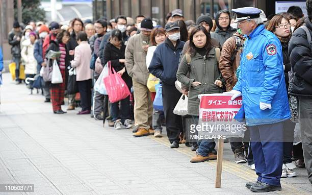 People queue outside a supermarket in Sendai Miyagi prefecture on March 20 2011 Workers were close to restoring power to a nuclear plant's...