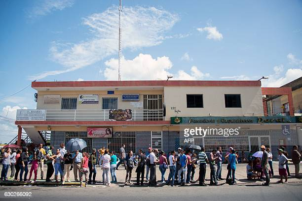 People queue outside a supermarket to buy basic food and household items after massive lootings took place in Ciudad Bolivar Bolivar state Venezuela...